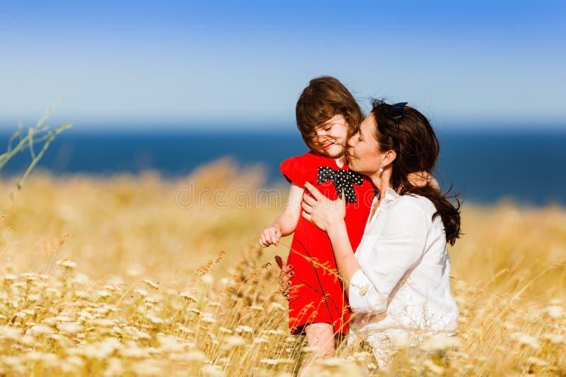 一件红色礼服和她的母亲的小女孩 免版税库存照片