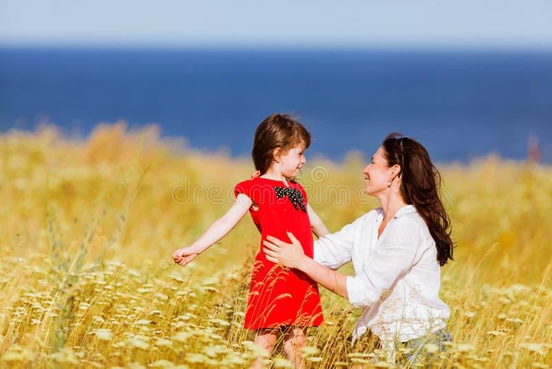 一件红色礼服和她的母亲的小女孩 库存照片