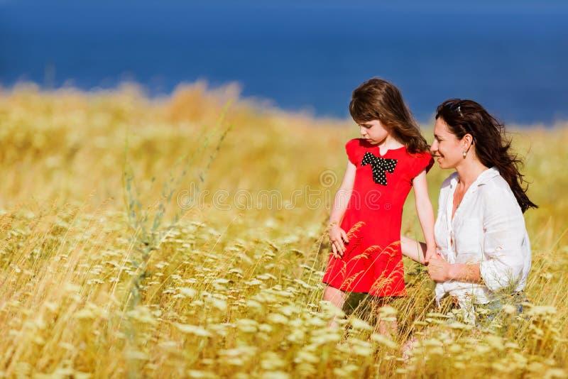 一件红色礼服和她的母亲的小女孩 库存图片