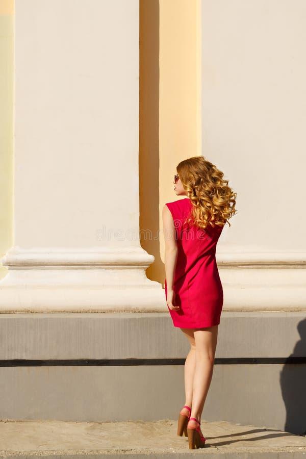 一件红色礼服的女孩有卷发的 免版税库存照片