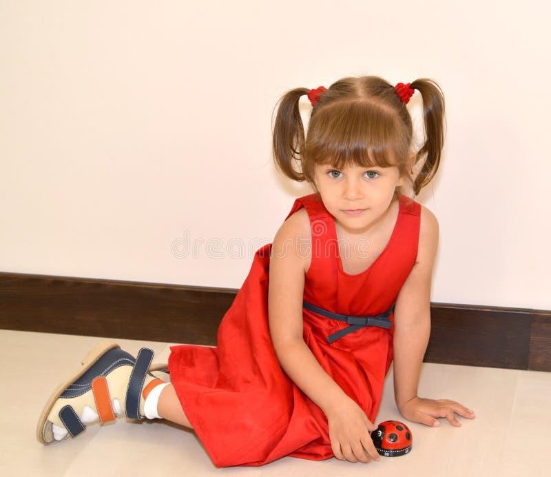 一件红色礼服的小女孩坐与玩具的一个地板 免版税库存照片