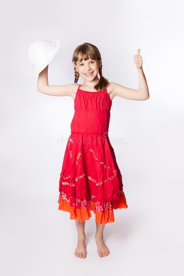 一件红色礼服的愉快的小女孩 免版税图库摄影