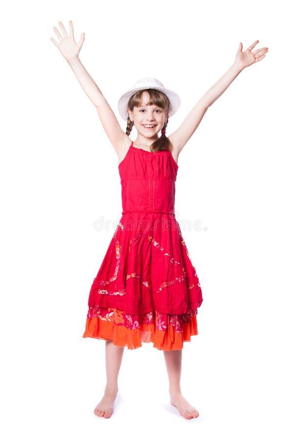 一件红色礼服的愉快的小女孩 图库摄影
