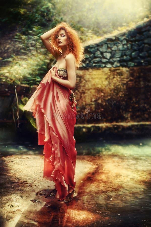 一件红色礼服的端庄的妇女在自然 库存图片