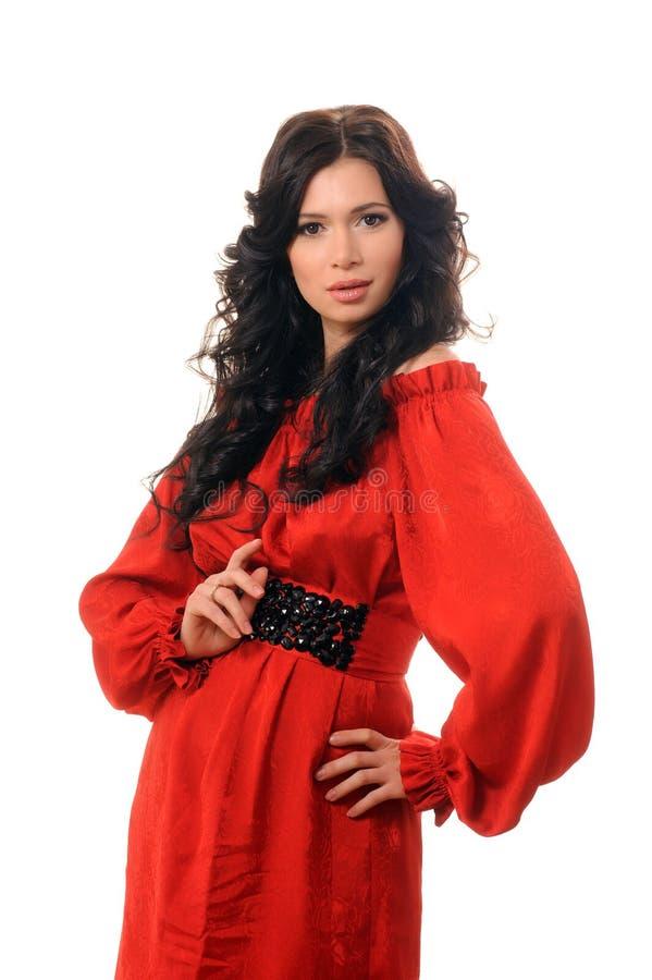 一件红色礼服的美丽的女孩在白色背景。 免版税库存图片