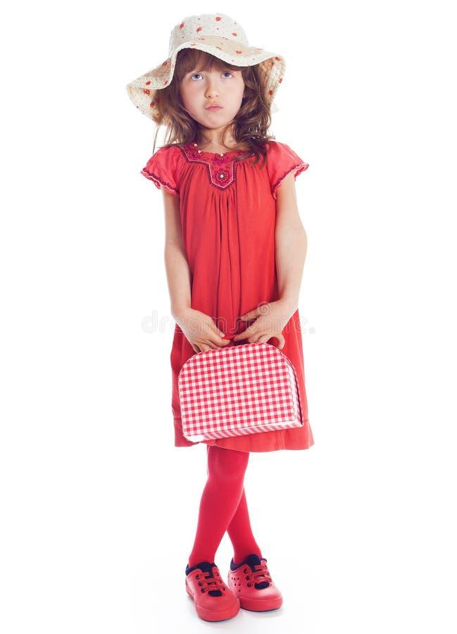 一件红色礼服的美丽的女孩带着手提箱 库存照片