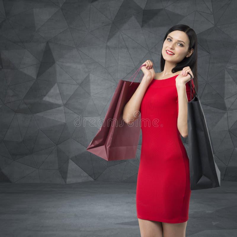 一件红色礼服的美丽的妇女拿着花梢购物袋 当代背景 免版税图库摄影