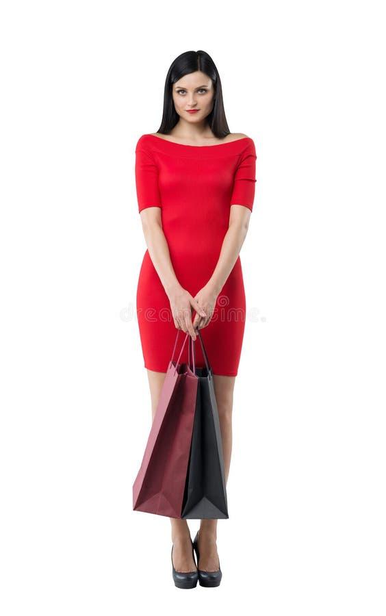 一件红色礼服的美丽的妇女拿着花梢购物袋 查出 图库摄影