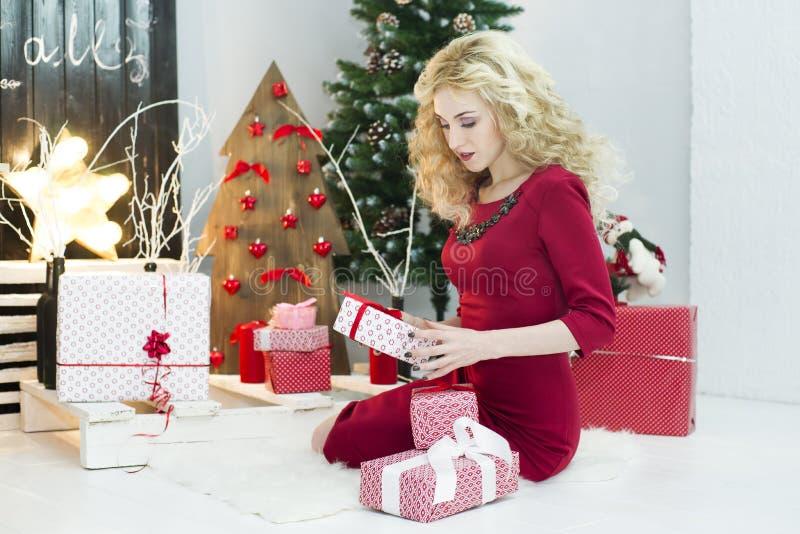 一件红色礼服的美丽的妇女有许多礼物盒的 库存照片