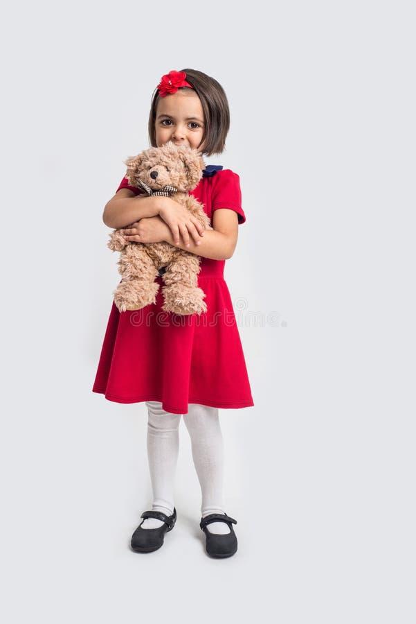 一件红色礼服的美丽的小女孩有玩具熊的 免版税库存照片