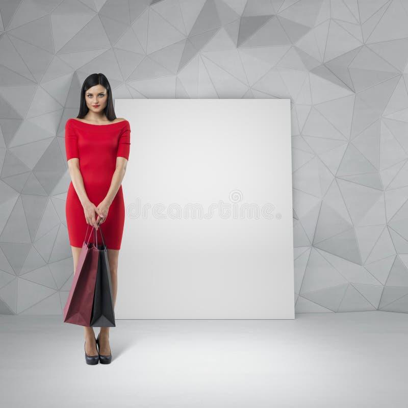 一件红色礼服的美丽的深色的妇女拿着花梢购物袋 库存图片
