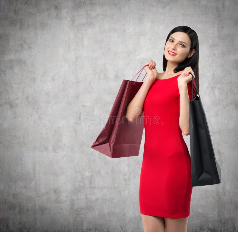 一件红色礼服的美丽的深色的妇女拿着花梢购物袋 免版税库存照片