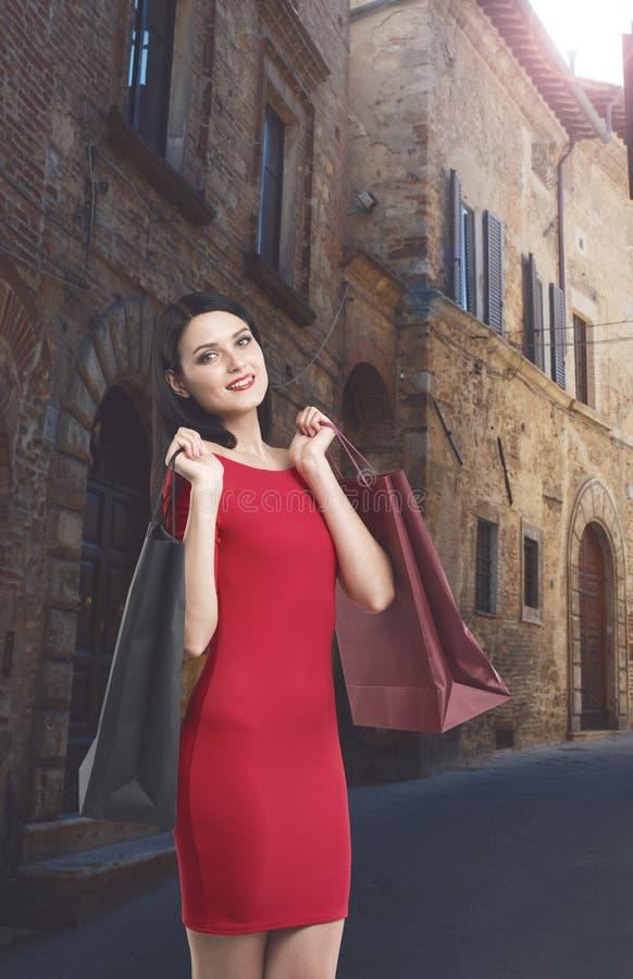 一件红色礼服的美丽的深色的妇女拿着花梢购物袋 免版税库存图片