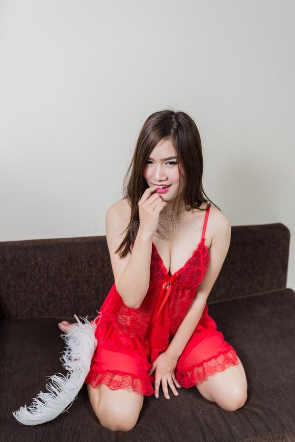 一件红色礼服的豪华红头发人妇女在棕色长沙发 免版税库存图片