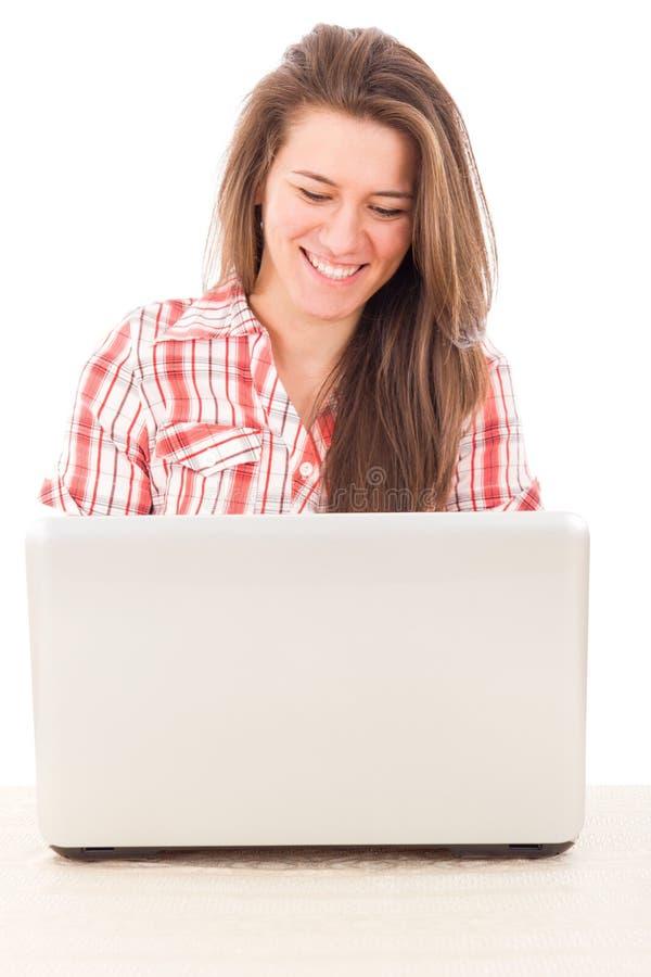 一件红色衬衣的微笑的妇女有膝上型计算机的 库存图片