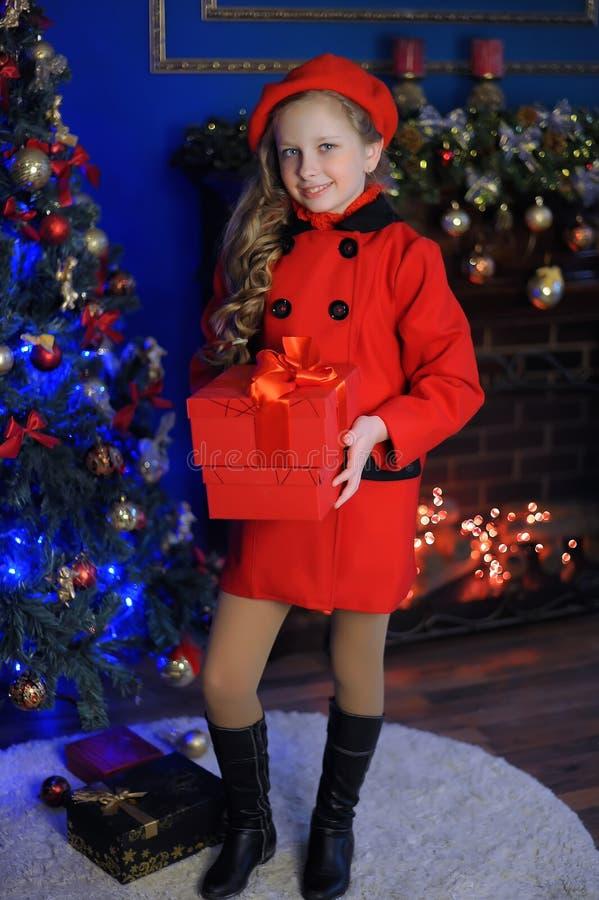 一件红色贝雷帽和外套的圣诞节女孩 免版税库存照片