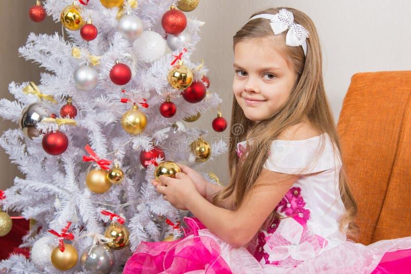 一件美丽的礼服的七年女孩对待圣诞节玩具和调查框架 免版税库存图片