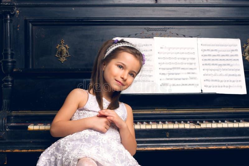 一件美丽的礼服的女孩坐在钢琴 免版税库存图片