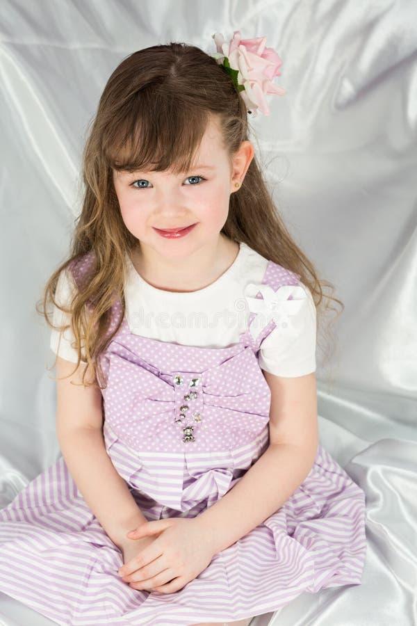 一件美丽的礼服的小女孩有花的 免版税库存图片
