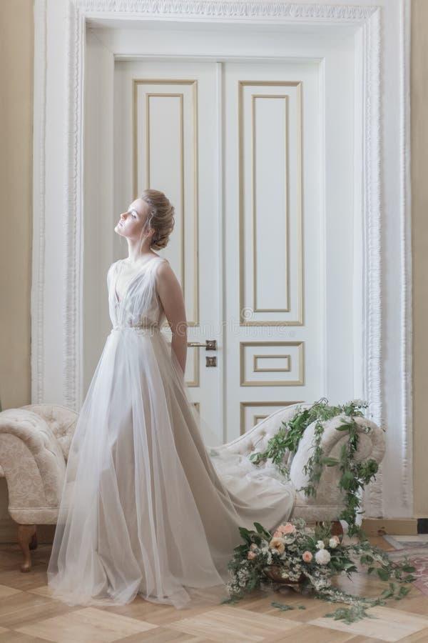 一件美丽的通风礼服的美丽的女孩新娘在米黄颜色,婚姻仿照boho样式 图库摄影