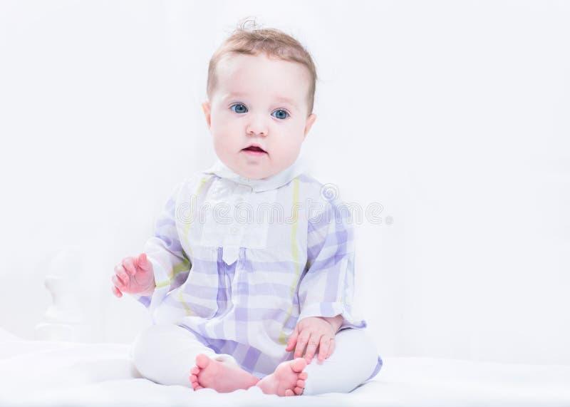 一件美丽的紫色礼服的可爱的女婴 图库摄影