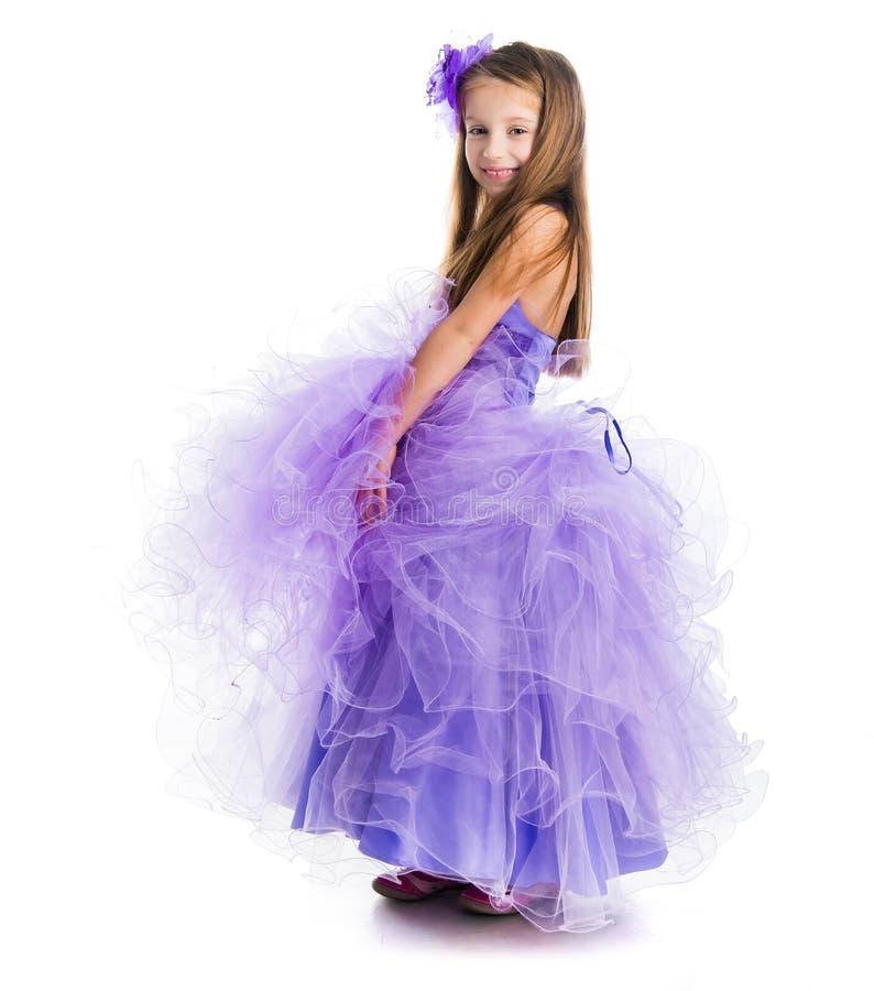 一件美丽的紫色礼服的小女孩 免版税库存图片