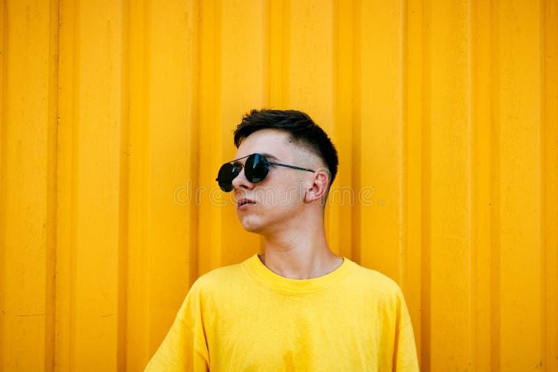 一件肮脏的黄色T恤杉和太阳镜的时髦的严肃的人 免版税库存图片