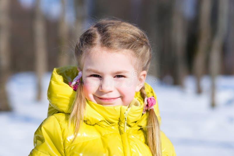 一件黄色冬天夹克的可爱的小女孩 库存图片