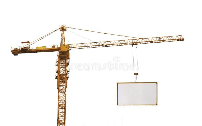 一黄色卷扬的起重机和广告hoardin 库存图片