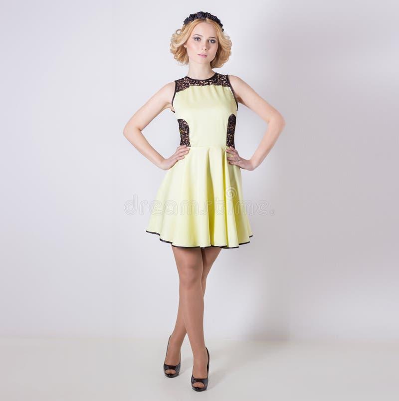 一件黄色夏天礼服的美丽的可爱的柔和的典雅的年轻白肤金发的妇女有pricheskoyi在她的头发的花花圈的 库存照片