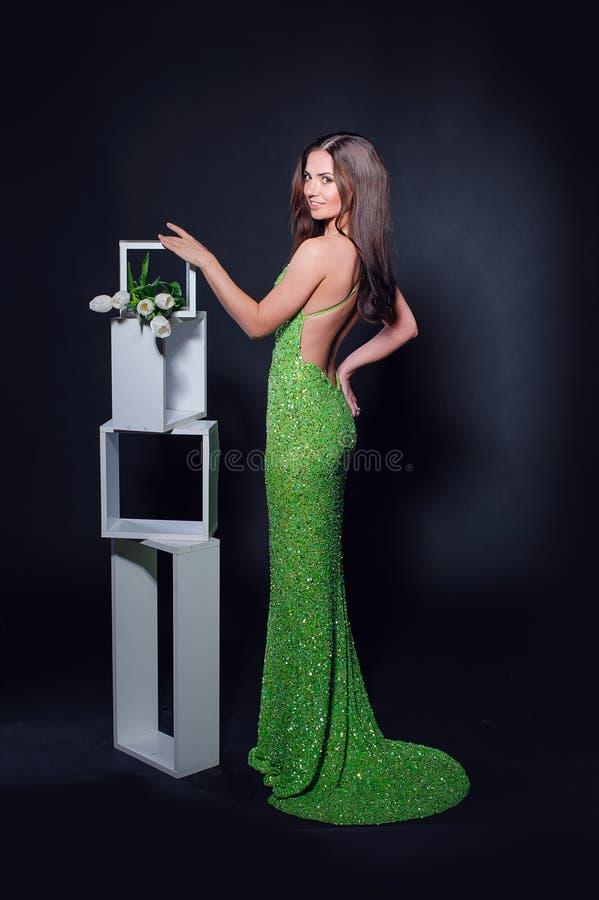 一件绿色晚礼服的美丽的妇女在黑背景 免版税库存照片
