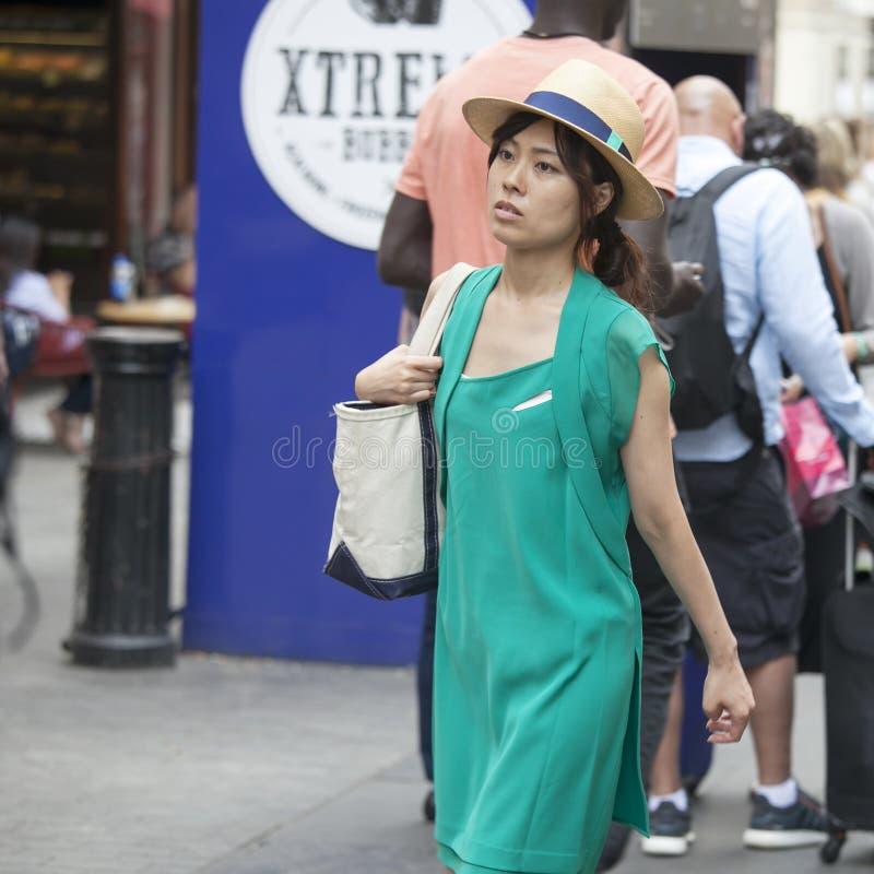 一件绿色礼服和草帽的美丽的严肃的亚裔女孩在莱斯特广场附近穿过路 图库摄影