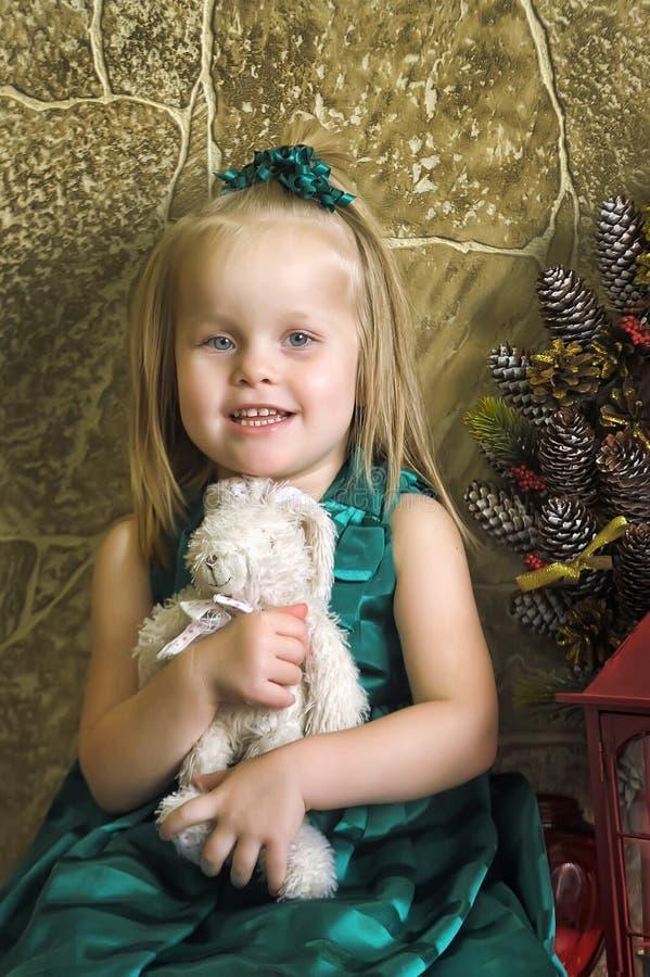 一件绿色礼服的小女孩用玩具野兔 库存图片