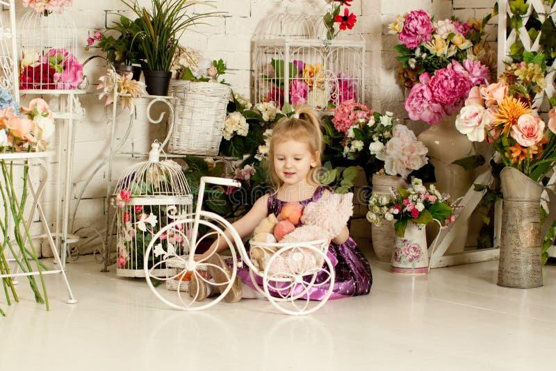 一件紫色礼服的小白肤金发的女孩 春天 免版税库存照片