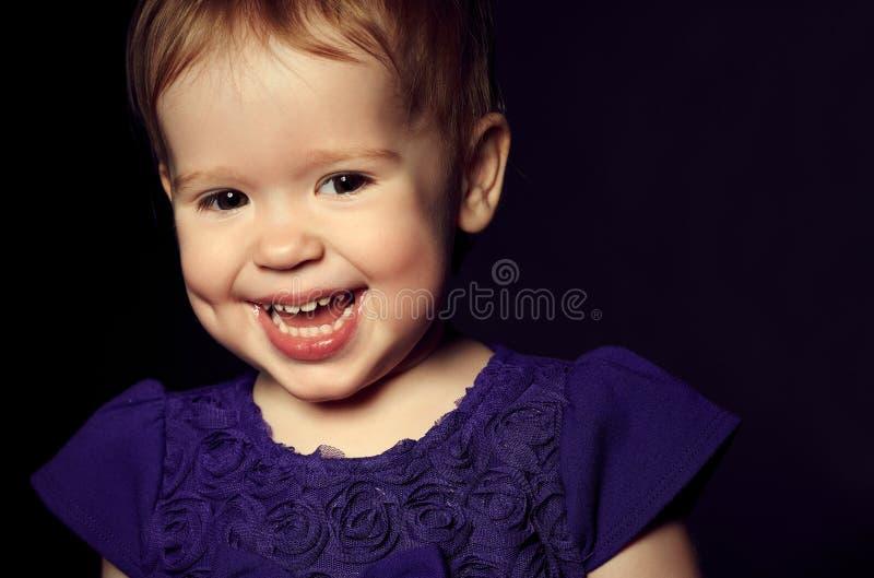 一件紫色礼服的美丽的愉快的小女孩 免版税库存图片