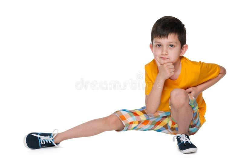 一件黄色衬衣的体贴的小男孩 免版税库存图片