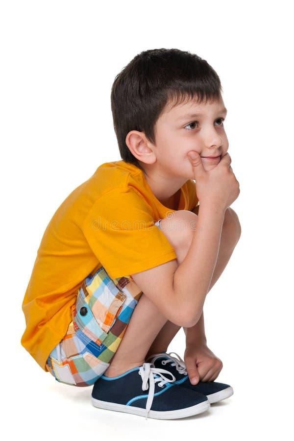 一件黄色衬衣的沉思小男孩 免版税库存照片