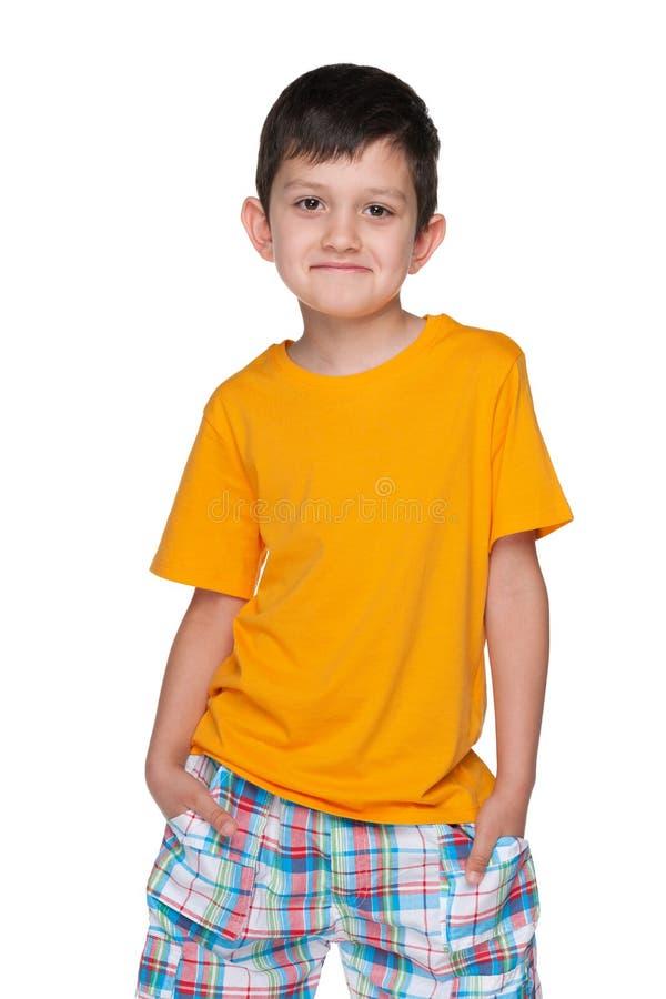 一件黄色衬衣的淘气年轻男孩 免版税库存照片