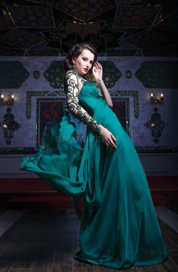 一件绿色长的礼服的美丽的妇女在背景富有地 库存图片