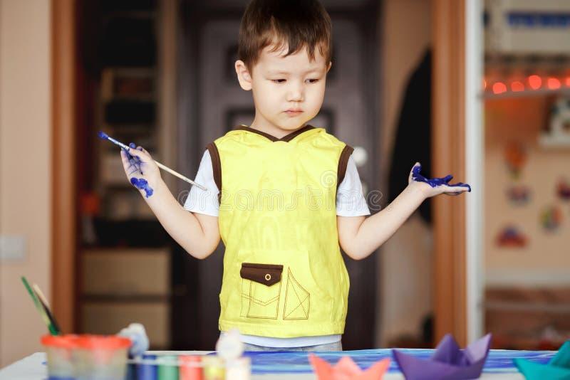 一件黄色T恤杉的小男孩弄脏了与油漆 免版税库存照片