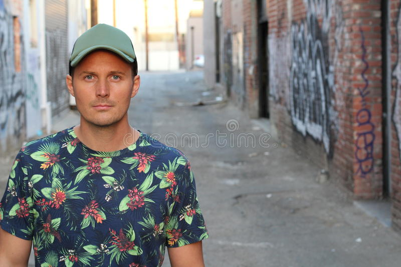 一件花卉T恤杉和一个棒球帽的运动人在与拷贝空间的都市背景 免版税图库摄影