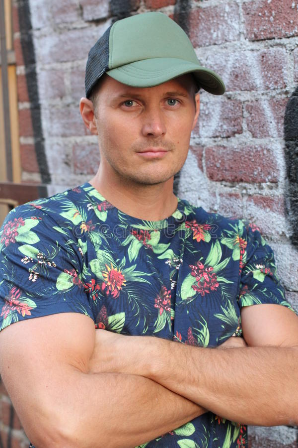 一件花卉T恤杉和一个棒球帽的运动人在都市背景 免版税库存照片