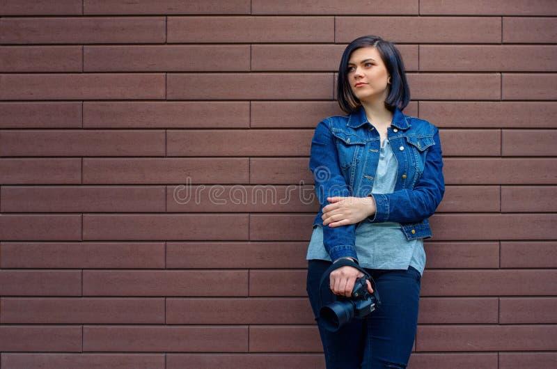 一件蓝色牛仔裤夹克的体贴的女孩有数字照相机的 免版税库存照片