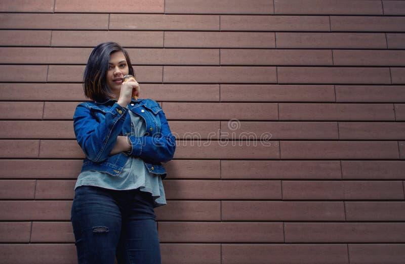 一件蓝色牛仔裤夹克的女孩有可口甜冰淇凌的 免版税库存图片