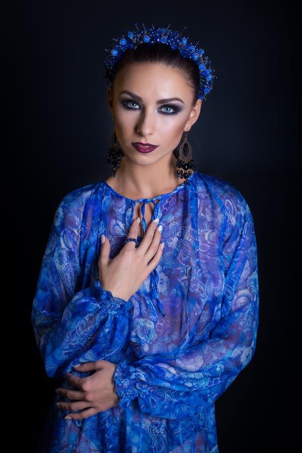 一件蓝色礼服有一个蓝色外缘的和设计耳环的美丽的性感的端庄的妇女在黑背景的演播室 免版税库存图片