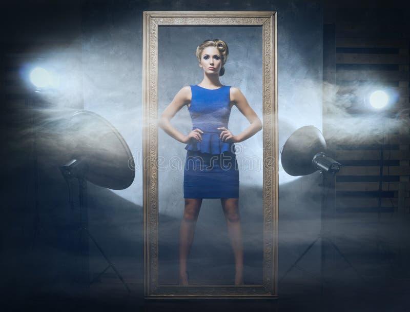一件蓝色礼服的一名妇女在魅力演播室背景 免版税库存图片