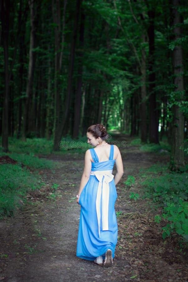 一件蓝色礼服的女孩走在绿色森林的转过来 免版税库存照片