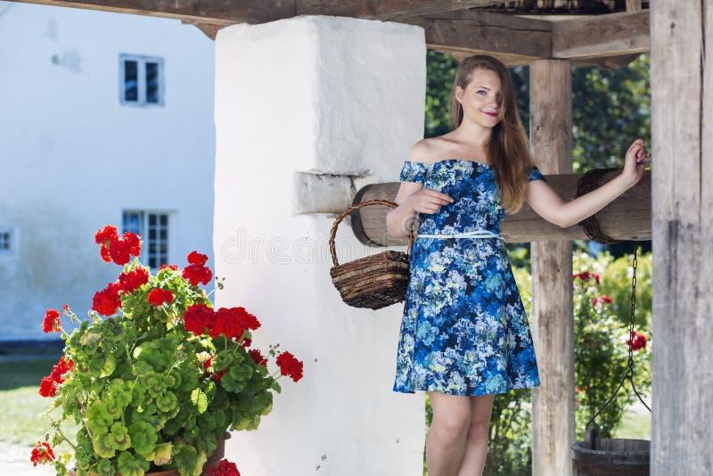 一件蓝色礼服的妇女有篮子的 免版税图库摄影