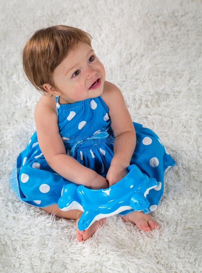 一件蓝色礼服的小女孩坐床并且查寻 免版税库存图片