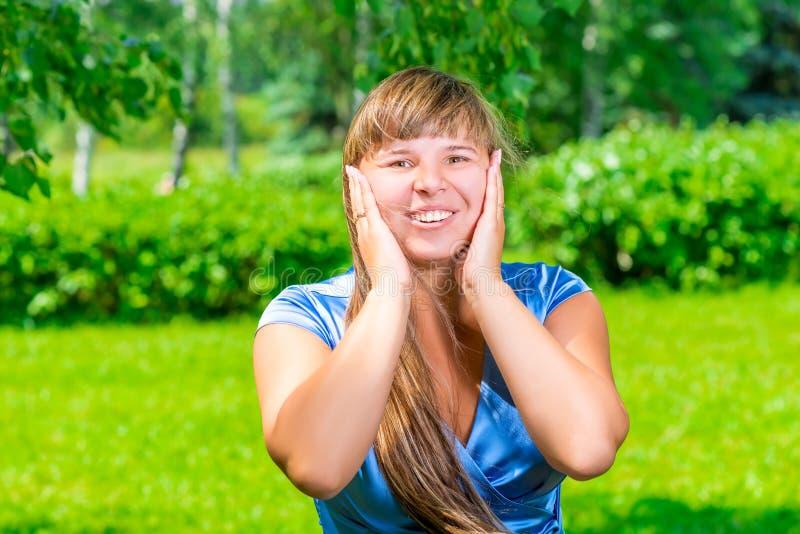 一件蓝色礼服的美丽的女孩在公园 库存图片
